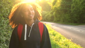 Weibliches Land der jungen Frau des schönen glücklichen Mischrasse Afroamerikanermädchenjugendlichen, das mit rotem Rucksack wand stock footage