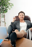 Weibliches Leitprogramm mit Füßen auf Schreibtisch Stockbild