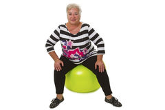 Weibliches älteres Sitzen auf Schweizer Ball Stockbilder