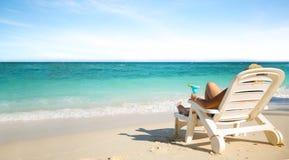 Weibliches Luxusc$ein Sonnenbad nehmen auf dem Strand Lizenzfreies Stockbild