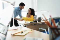 Weibliches Manager-Speaking With Mobile-Telefon und -kollege bei der Arbeit stockfotos