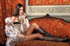 Weibliches Mode-Modell, das in einem Pelzmantel auf einem Weinlesesofa aufwirft Stockfotos