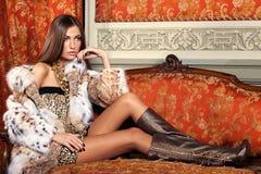 Weibliches Mode-Modell, das in einem Pelzmantel auf einem Weinlesesofa aufwirft Stockbilder