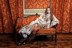Weibliches Mode-Modell, das in einem Pelzmantel auf einem Weinlesesofa aufwirft Alw Stockbilder