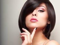 Weibliches Modell der sexy schwarzen kurzen Frisur, das mit dem Finger nahe dem Gesicht schaut Stockfotografie