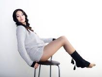 Weibliches Modell in der Wolljacke auf einem Stuhl Stockfoto
