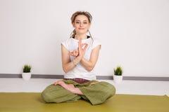 Weibliches Modell in der Yogahaltung im Studio Junge Frau, die ?bungen tut relax lizenzfreies stockbild
