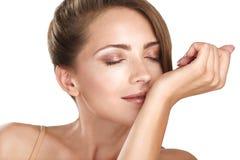 Weibliches Modell des schönen Brunette, das ihr Parfüm riecht Stockbild