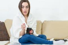Weibliches Modell fing die Kälte, die zu Hause mit weißer Decke umfasst wurde stockfotografie