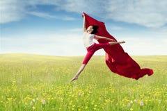 Weibliches Modell mit Gewebe springt am Feld Stockfotografie