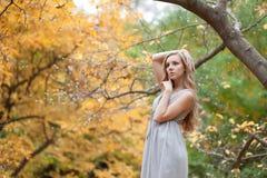 Weibliches Modell wickelt seine Arme ein, die sein Hauptgesicht, eine Hand auf t umarmen Lizenzfreie Stockfotos