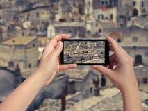 Weibliches nehmendes Bild der alten Stadt Matera in Italien am Handy Landschaft der alten Stadt Matera am intelligenten Telefon Lizenzfreie Stockbilder