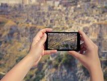 Weibliches nehmendes Bild der alten Stadt Matera in Italien am Handy Landschaft der alten Stadt Matera am intelligenten Telefon Lizenzfreies Stockbild