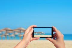 Weibliches nehmendes Bild des tropischen Strandes mit großen Strohregenschirmen am Handy Lizenzfreies Stockfoto