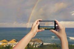 Weibliches nehmendes Bild am Handy des doppelten Regenbogens über Ozean und des tropischen Strandes mit Regenschirmstühlen und -t Stockbild