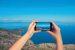 Weibliches nehmendes Bild von Landschaftsgriechischer Insel am Handy Landschaft von Meer und von Berg auf Smartphone Stockfotos