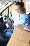 Weibliches Paket Kurier-In Van With Digital Tablet Delivering zu Stockfotografie