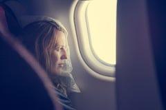 Weibliches Passagierschlafen umfasst mit Decke Stockfotos