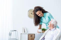Weibliches Pflegekraftumhüllungsnachmittagstee zum Patienten Lizenzfreie Stockbilder