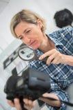 Weibliches photphrapher, das Kamera durch Lupe betrachtet Lizenzfreie Stockfotografie