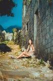 Weibliches Porträt der jungen romantischen Frau, die auf ältester Steinstraße in der alten Stange, Montenegro sitzt Sommerreisen Stockbild