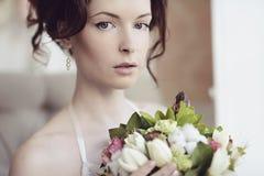 Weibliches Porträt netter Dame mit Blumenstrauß zuhause Lizenzfreie Stockbilder