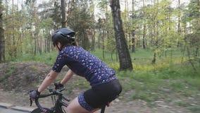 Weibliches Radfahrerreitfahrrad im Park Abschluss herauf Seitenansicht folgen Schuss Radfahrenkonzept stock footage