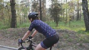 Weibliches Radfahrerreitfahrrad im Park Abschluss herauf Seitenansicht folgen Schuss Radfahrenkonzept Langsame Bewegung stock footage