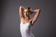 Weibliches Schönheitsporträt des jungen jugendlich mit den Brötchenhänden oben auf grauem Hintergrund Stockfotos