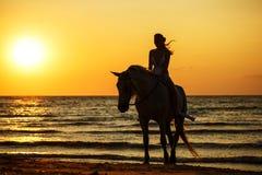 Weibliches Schattenbild auf einem Pferd bei Sonnenuntergang durch das Meer lizenzfreie stockfotos