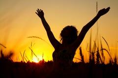 Weibliches Schattenbild auf Sonnenuntergang auf wheaten Feld Stockfotografie