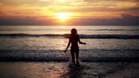 Weibliches Schattenbild, das auf dem Meer auf Sonnenuntergang läuft stock video footage