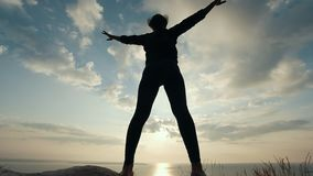 Weibliches Schattenbild, das körperliche Bewegung gegen den Sonnenaufgang tut stock video footage