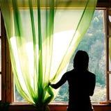 Weibliches Schattenbild am geöffneten Fenster Lizenzfreie Stockfotos