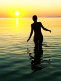 Weibliches Schattenbild mit dem Sonnenuntergang Lizenzfreie Stockfotos