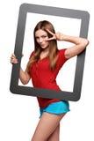 Weibliches Schauen durch den Rahmen, der Daumen aufgibt Stockfoto