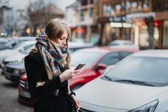 Weibliches schauendes tragbares Gerät auf Schalmantel der jungen kaukasischen Frau der Herbststraße tragendem Woll lizenzfreies stockbild