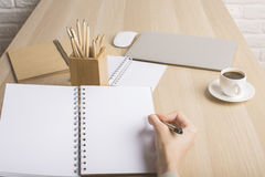 Weibliches Schreiben in der Notizblockseite Stockfotos
