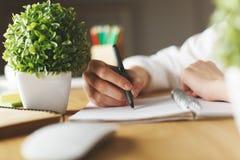 Weibliches Schreiben im Notizblock Lizenzfreie Stockfotos