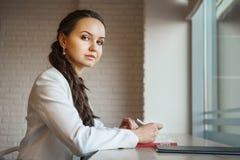 Weibliches Schreiben im Tagebuch, das auf Schreibtisch und in camera schauen ist stockbild