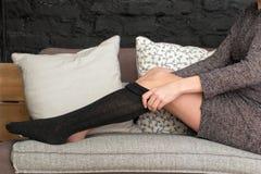 Weibliches Setzen auf schwarze Strümpfe Lizenzfreies Stockbild