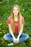 Weibliches Sitzen auf dem Feld des Löwenzahns Lizenzfreie Stockfotografie