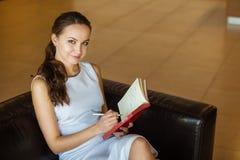 Weibliches Sitzen auf schwarzem Sofa in den weißen Luxuskleider- und nehmenanmerkungen stockfotos