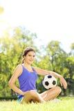 Weibliches Sitzen des jungen Athleten auf einem grünes Gras- und Holdingball I Lizenzfreies Stockbild