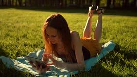 Weibliches Sitzen im Park unter den Bäumen und benutzen das Internet auf Tablette stock footage