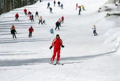 Weibliches Skifahrerskifahren hinunter ein piste lizenzfreie stockfotos