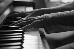 Weibliches spielendes Schwarzweiss-Klavier Stockbilder