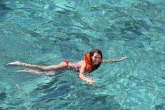 Weibliches touristisches Lernen, unter Verwendung einer Schwimmweste zu schwimmen Stockbilder