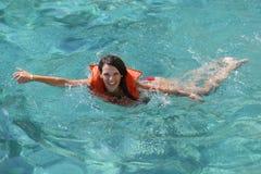 Weibliches touristisches Lernen, unter Verwendung einer Schwimmweste zu schwimmen Stockbild