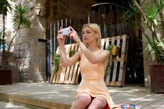 Weibliches touristisches nehmendes Bild mit ihrem intelligenten Telefon beim am schönen sonnigen Tag draußen sitzen Stockfoto